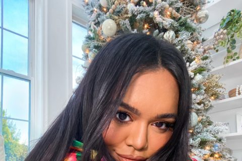 Nabela Noor sitting in front of Christmas tree