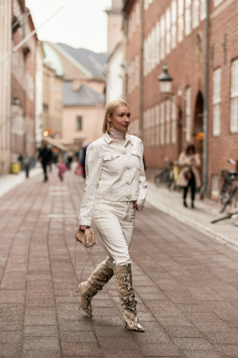 white denim pants tucked into boots
