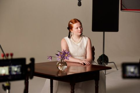 A model sitting behind a table at the H&M x Simone Rocha campaign shoot
