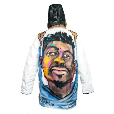 A white Wuxly coat features artwork, a portrait of a Black man, by local Toronto artist Jabari Elliott on the back