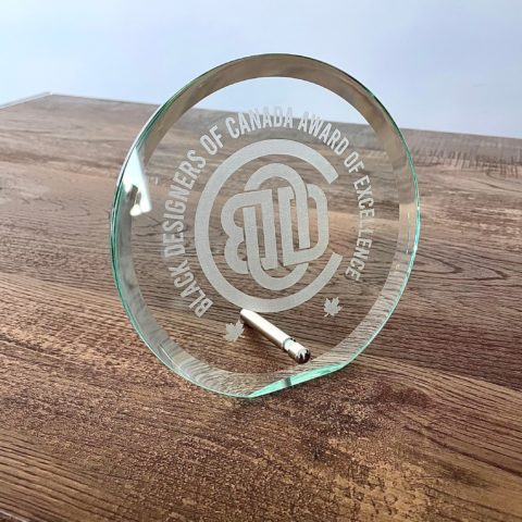 Hand-cut glass award, sitting on a wooden table, given to recipients of the Black Designers of Canada Award of Excellence