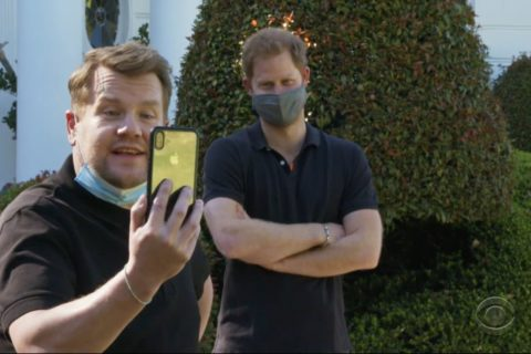 James Corden holds up a phone while he and Prince Harry are on a video call in this still from the new Prince Harry James Corden Interview