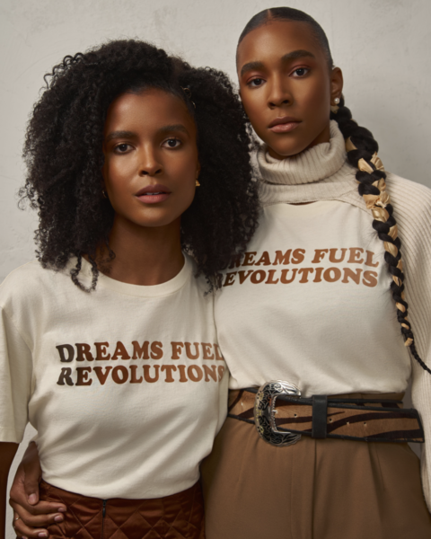 Two Black women wearing Roots T-shirts designed in collaboration with Revolutionnaire