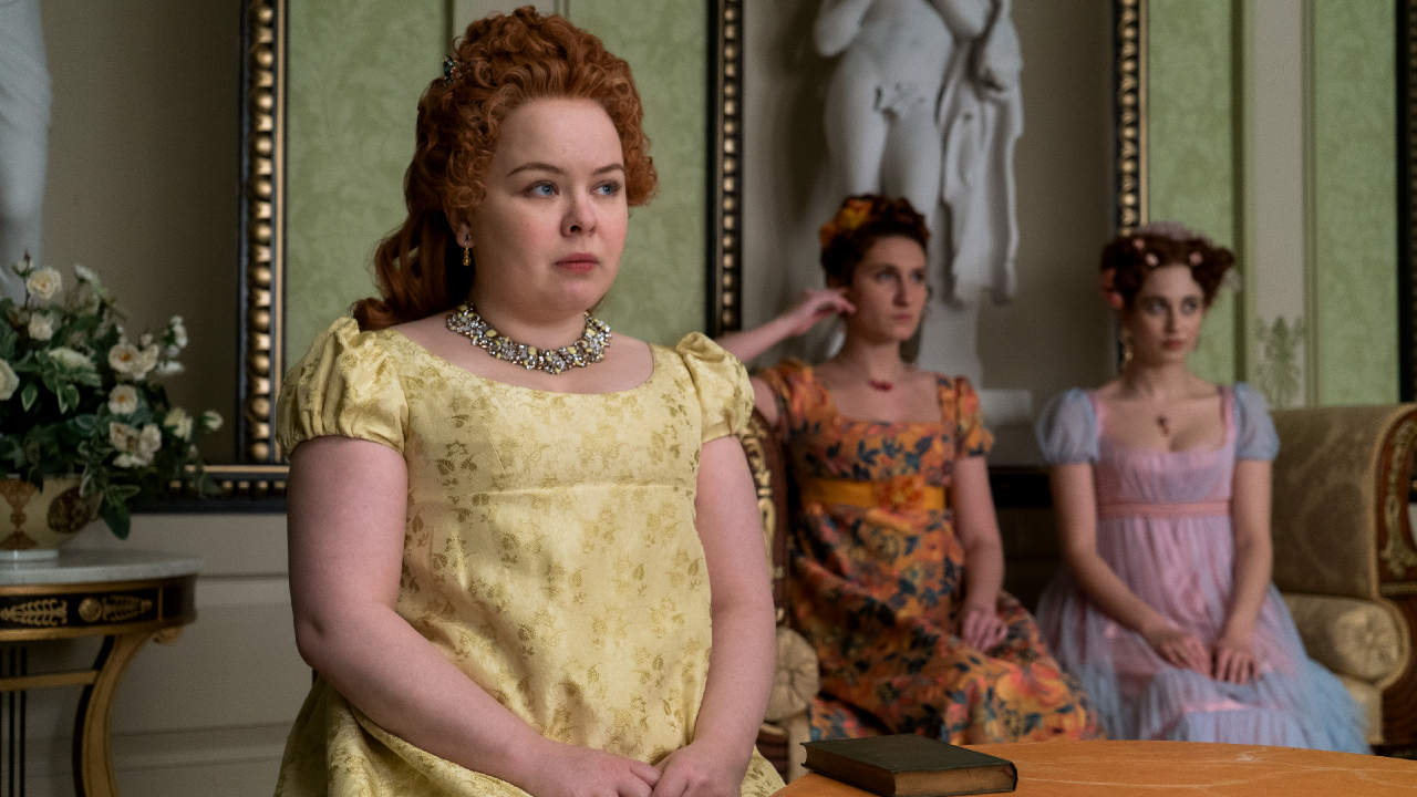 Nicola Coughlan as Penelope Featherington sits at a table with Bessie Carter as Prudence Featherington and Harriet Cains as Phillipa Featherington in the background in episode 10 of Bridgerton