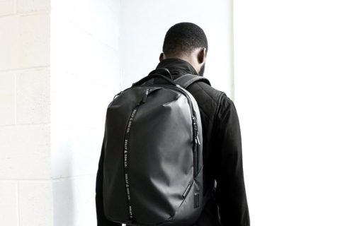 A man dressed in black wearing a black shiny backpack is pictured from the back against a white background