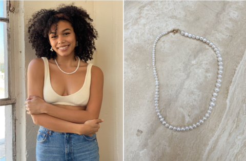 A woman wearing a pearl necklace and hugging herself