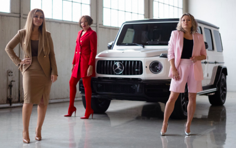 Three women posing in front of a Mercedes-Benz wearing Pink Tartan power suits