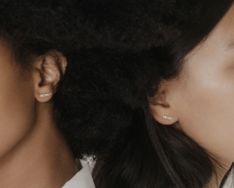 """A pair of Eriness earrings that say """"resist"""""""