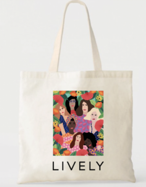 A tote bag with a colourful illustration of a group of women on the front