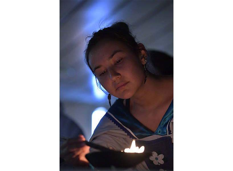 Jennifer Kilabuk lighting a qulliq, a traditional oil lamp, used in a Inuit Welcome Ceremony on board the Adventure Canada cruise (Photo: Michelle Valberg)